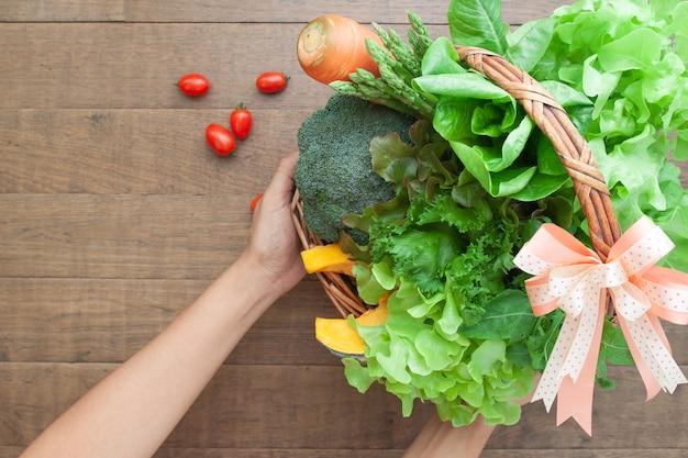 De handen die van de bovenaanzichtvrouw de giftreeks van de groentenmand houden
