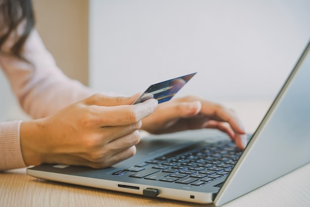 De handen die van de close-upvrouw een creditcard houden en computertoetsenbord gebruiken