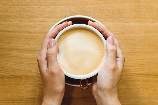 De handen die van de hoogste meningsvrouw een kop van koffie met schuim over houten lijst houden