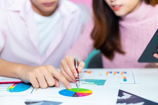 De handen die van de jonge werknemer op document grafieken richten