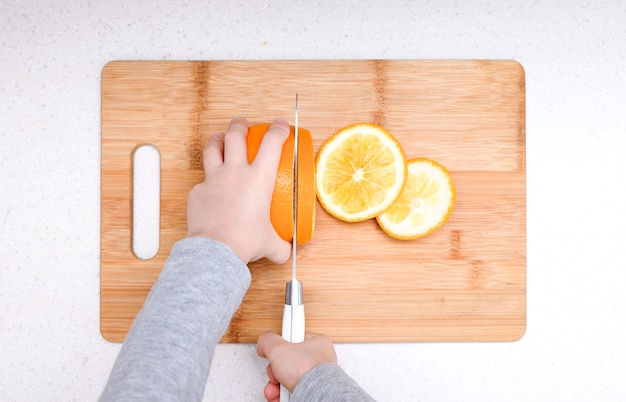 De handen die van de jongen verse sinaasappel op keuken snijden