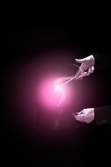 De handen die van de tovenaar magische truc over magische hoge zijden uitvoeren tegen zwarte achtergrond