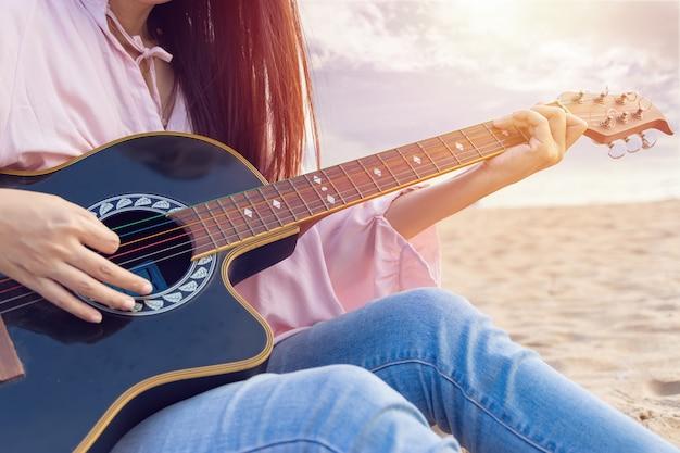 De handen die van de vrouw akoestische gitaar op het strand spelen