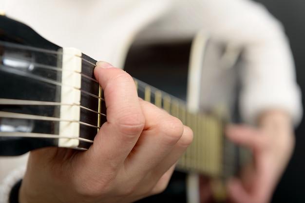 De handen die van de vrouw akoestische gitaar spelen, sluiten omhoog