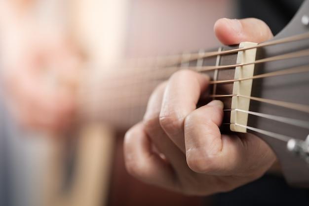 De handen die van de vrouw akoestische gitaar spelen.