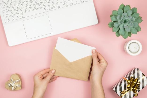 De handen die van de vrouw ambachtenvelop met copyspace op roze de bovenkantmening houden van de pastelkleurlijst. plat lag compositie voor valentijnsdag.