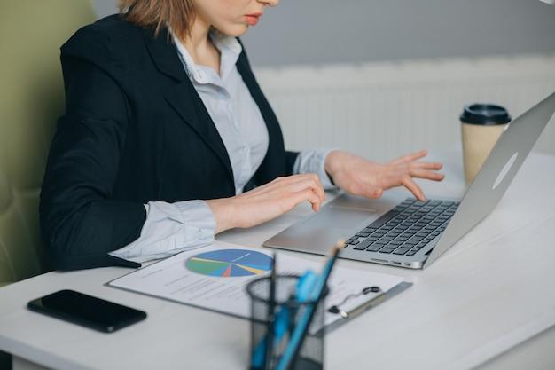 De handen die van de vrouw bij laptop toetsenbord in bureau typen. close-up shot vergrendeld.