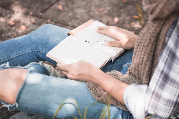 De handen die van de vrouw boek houden