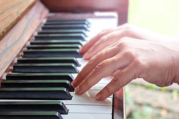 De handen die van de vrouw de piano spelen. retro stijl. warme kleur afgezwakt.