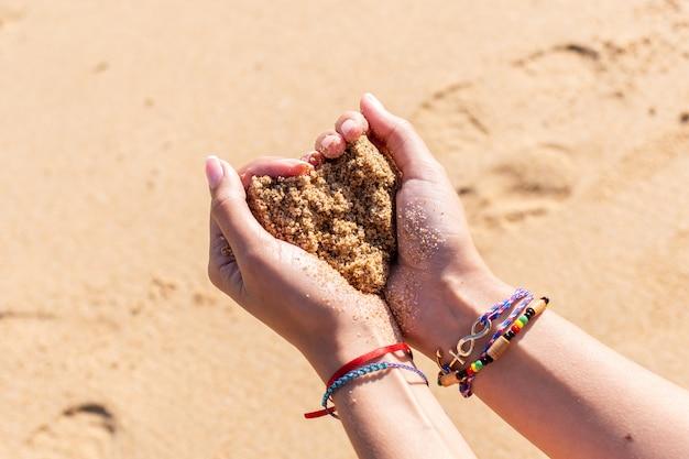 De handen die van de vrouw een hart van zand op het strand maken