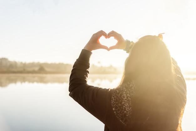 De handen die van de vrouw een hartvorm vormen op ochtendzonsopgang.
