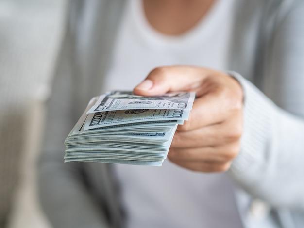 De handen die van de vrouw geld voorstellen ons dollarrekeningen aan u.
