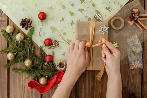 De handen die van de vrouw kerstmisgift verpakken, sluiten omhoog. onbereide kerstcadeautjes op houten met decorelementen en items, bovenaanzicht. kerstmis of nieuwjaar diy-verpakking.