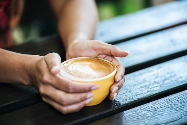 De handen die van de vrouw kop van koffie houden bij koffie