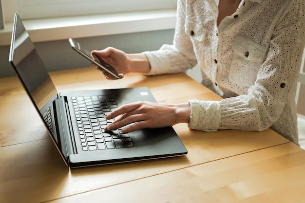 De handen die van de vrouw laptop en smartphone op bureau in huisbinnenland gebruiken