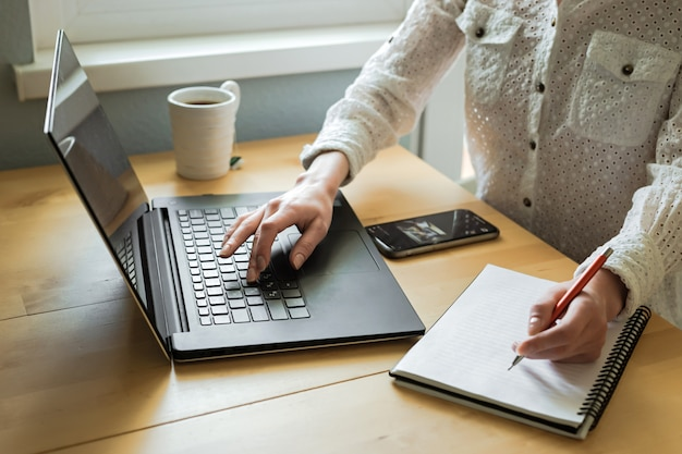 De handen die van de vrouw laptop op bureau in huisbinnenland met behulp van