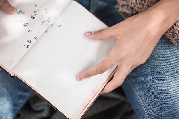 De handen die van de vrouw notitieboekje houden
