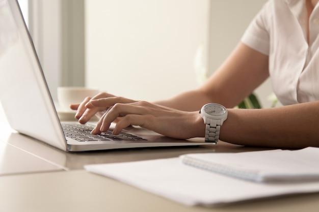 De handen die van de vrouw op laptop op het werk typen