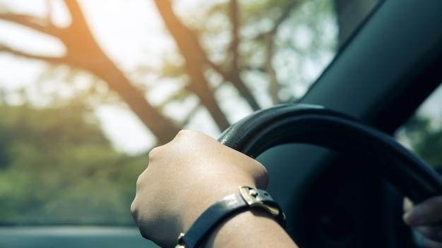 De handen die van de vrouw op zwart stuurwiel houden terwijl het drijven van een auto