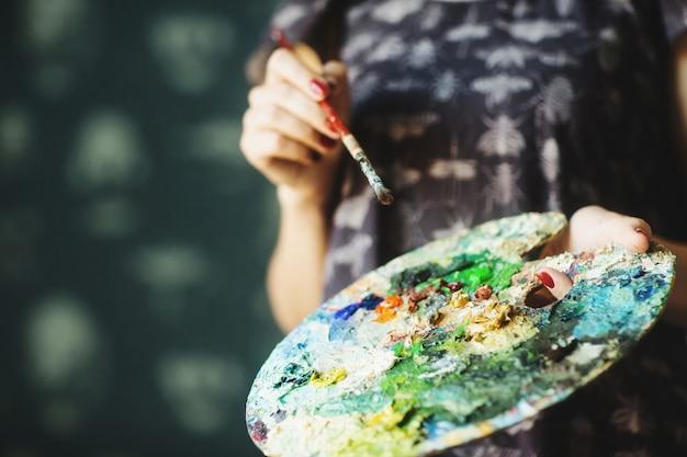 De handen die van de vrouw penseel en palet met olieverven houden. detailopname. kunst concept