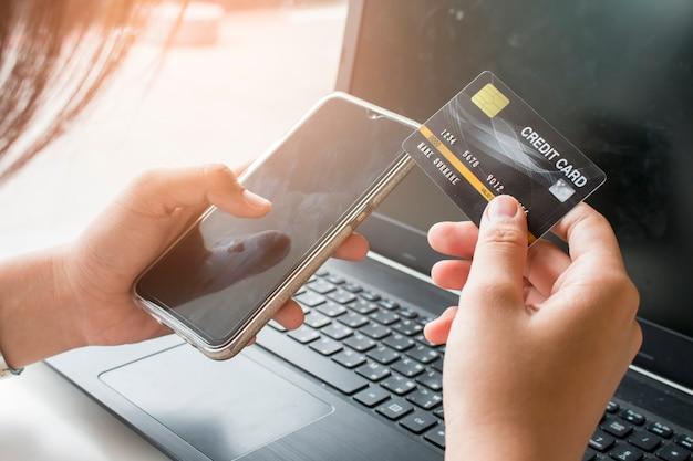 De handen die van de vrouw smartphone houden en creditcard gebruiken