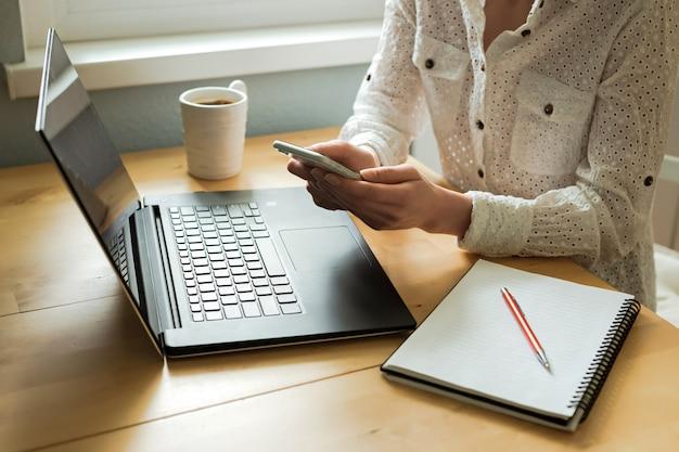 De handen die van de vrouw smartphone, laptop op bureau in huisbinnenland gebruiken