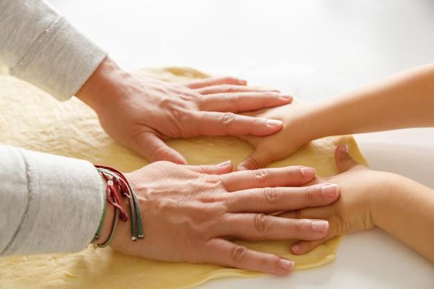 De handen die van een moeder en van een kind samen pizzadeeg uitrekken