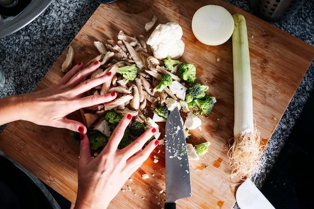 De handen die van een vrouw paddestoelen en groente in een keuken snijden