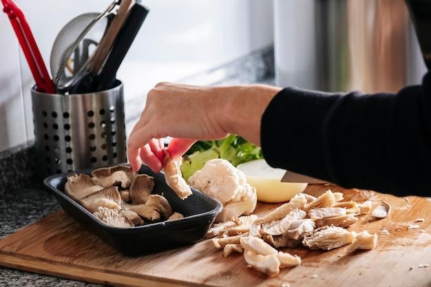 De handen die van een vrouw paddestoelen en plantaardige uikool en prei in een keuken snijden