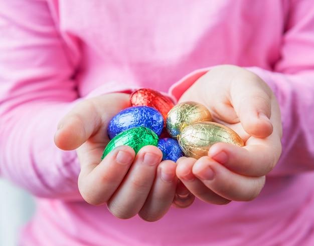 De handen die van het kind chocoladepaaseieren houden