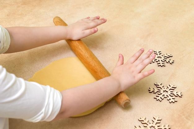 De handen die van het kind deeg met deegrol vellen