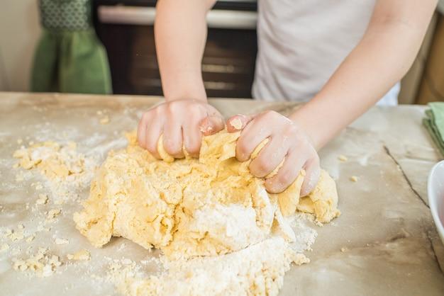 De handen die van het kind deeg thuis in de keuken kneden. thuis koken
