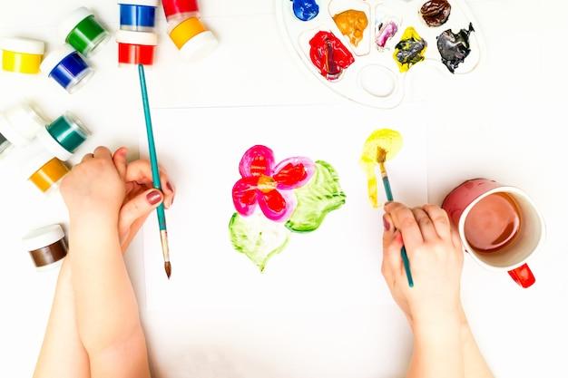 De handen die van het kind een bloem schilderen