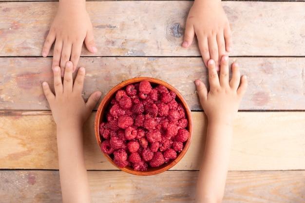 De handen die van het kind houten komhoogtepunt van mooie verse sappige aardbeien houden. boven tafelaanzicht
