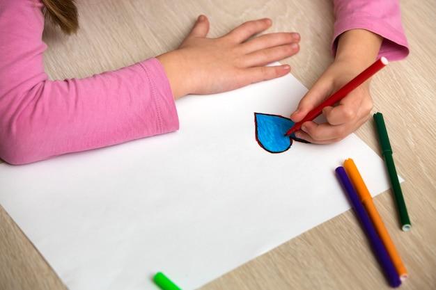 De handen die van het kindmeisje met kleurrijke potloden trekken schetsen blauw hart op witboek. kunstonderwijs, creativiteit concept.