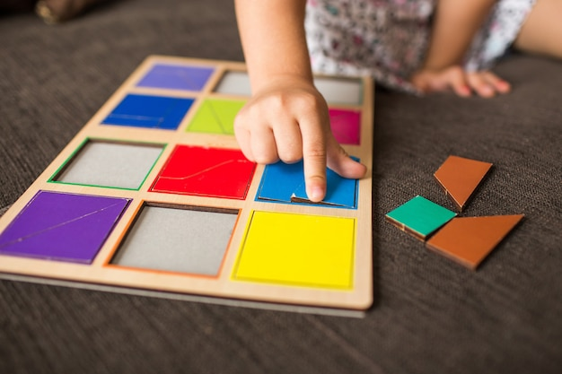 De handen die van het meisje met een houten mozaïek op een bank spelen. educatieve spellen. montessori preschool ontwikkelt zich vroeg