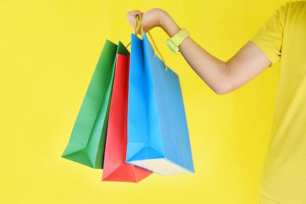 De handen die van het mooi kindmeisje het winkelen zak houden die op gele achtergrond wordt geïsoleerd.
