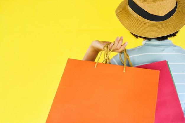 De handen die van het mooie kindmeisje het winkelen zak op geel houden