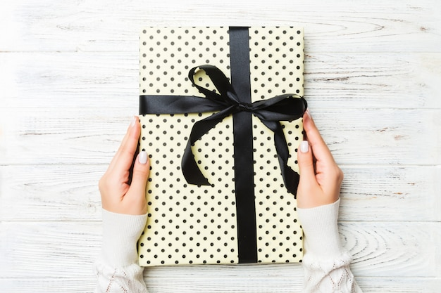De handen die van het wijfje gestreepte giftdoos met gekleurd lint op witte rustieke houten, kerstmisconcept of andere vakantie met de hand gemaakte huidige doos, concepten hoogste mening houden