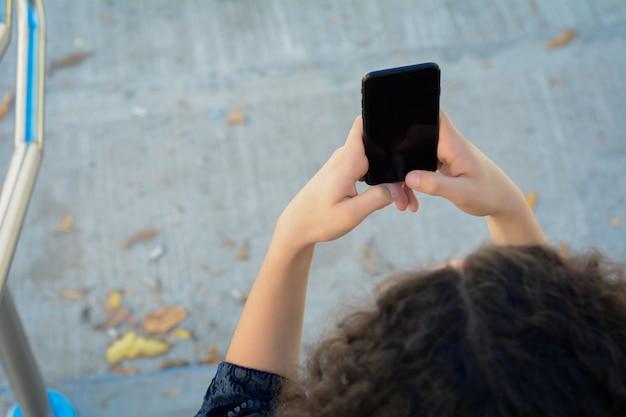 De handen die van jonge vrouwen smartphone houden.