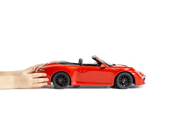 De handen die van kinderen een rode porsche carrera s 911 modelstuk speelgoedauto houden die op witte achtergrond wordt geïsoleerd.