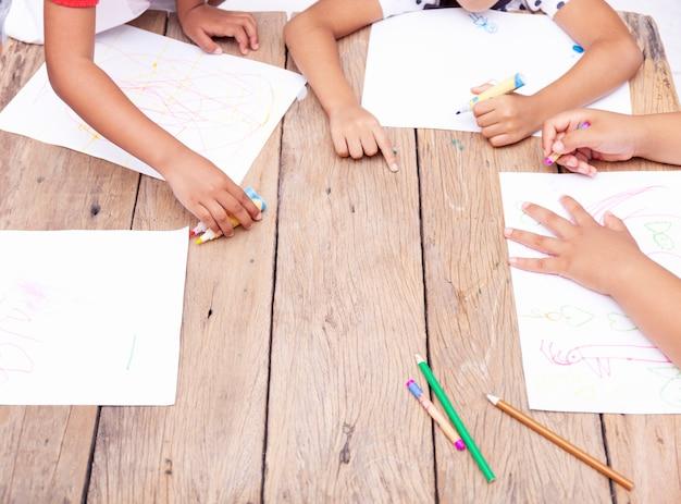 De handen die van kinderen met kleurpotloden op houten lijst trekken