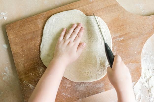 De handen die van kinderen ruw gerold deeg snijden