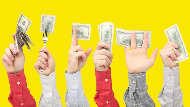 De handen die van mensen dollarbiljetten met geld op geel houden