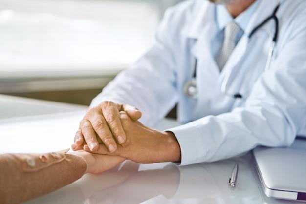 De handen die van vriendelijke mannelijke arts de hand van de vrouwelijke patiënt houden voor aanmoediging en empathie. partnerschap, vertrouwen en concept van medische ethiek. minder nieuws en ondersteuning voor slecht nieuws. patiënt juichen en ondersteunen