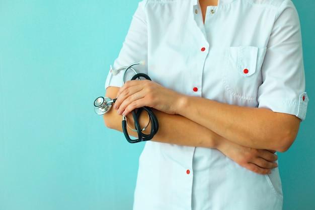 De handen die van vrouwelijke artsen stethoscoop op lichtblauwe muur houden