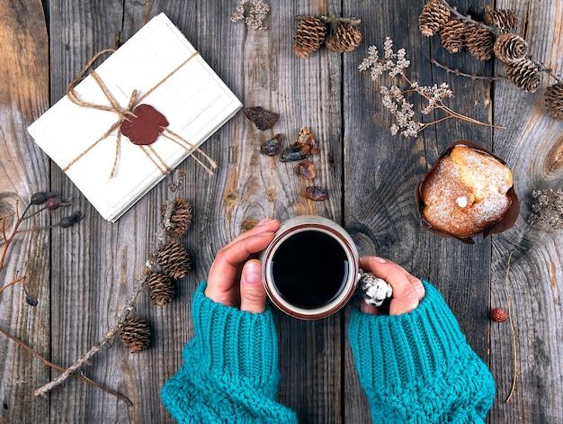 De handen die van vrouwen een ceramische mok met zwarte koffie, grijze houten lijst houden
