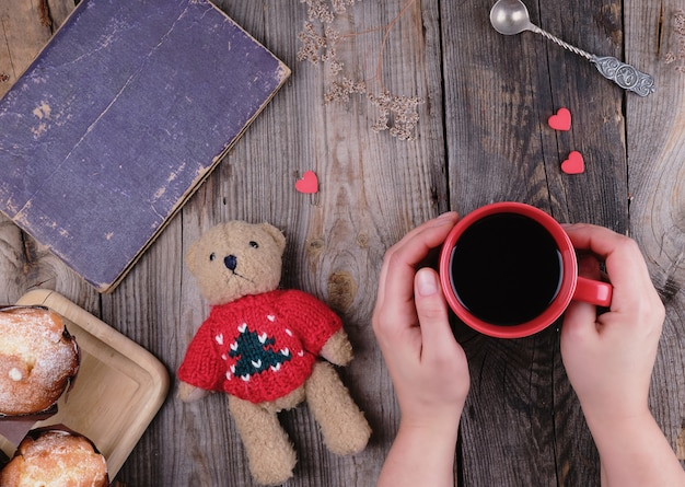 De handen die van vrouwen een rode ceramische mok met zwarte koffie houden