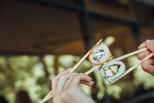 De handen die van vrouwen houten stokken met sushi houden