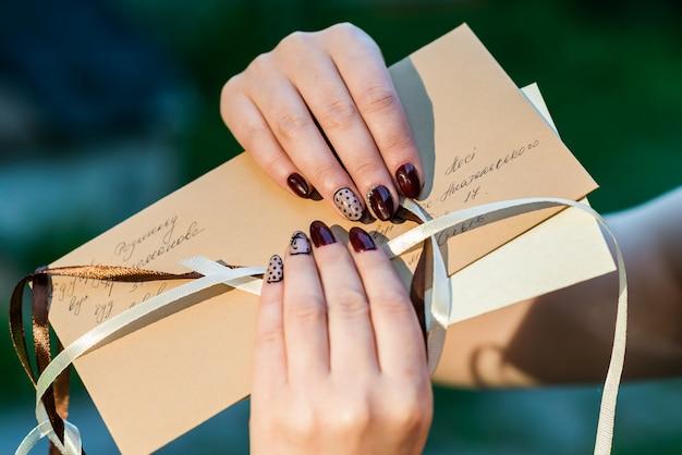 De handen die van vrouwen postenvelop houden